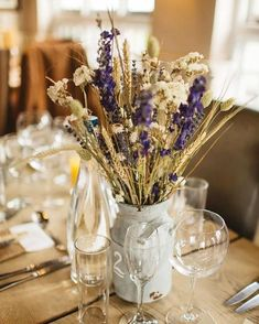 @curiouscountry posted to Instagram: I love so many things about this dried flower centerpiece-- the wheat and club wheat, the dried everlasting flowers, and the bright blue larkspur flowers come together so well.  I wouldn't mind sitting down to a meal with that table centerpiece to enjoy!  #driedwheat #larkspur #everlasting #driedflowers #centerpiece #weddinginspiration #floraldesign #flowerarrangement
