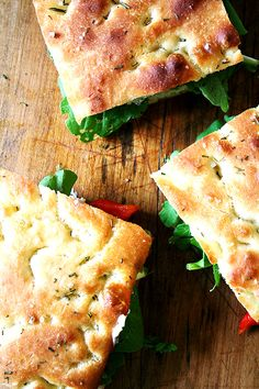 Focaccia bread, spreadable Swiss cheese, spinach leaves, fresh tomato slices, roasted red pepper slices, and sliced rotisserie chicken.