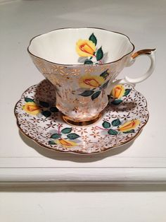 Royal Albert Gold Chintz and Yellow Rose Teacup and Saucer  Marked England   This set has a yellow Tea Rose surround against wonderful gold chintz. The deep foot line and high feather rest have generous gold work. Teacup and Saucer are finished with gold trim edge.