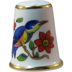Ansley England bone china thimble bluebird and flowers. This is a really lovely thimble.  It shows a Bluebird sitting on a branch that has bright  red