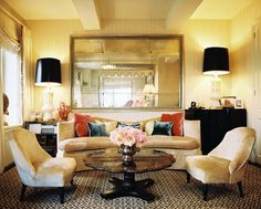 Bohemian Living Room Photo - A sitting area with a curved couch and a pair of upholstered chairs surrounding a scallop-edge coffee table