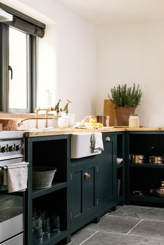 Reclaimed brass taps, a big farmhouse sink, simple deVOL Kitchen cupboards and natural stone flooring