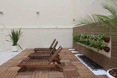 Condomínio Residencial Paraíso. Reforma em área de lazer. Espaço ao fundo do condomínio utilizado para um solarium, paisagismo feito em jardim vertical O deck feito em madeira plástica Rewood.