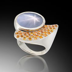 "Adam Neeley ""Stellar"" ring with a grey star sapphire complemented by pave set mandarin garnets"