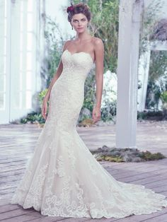 Lace artfully placed atop tulle adds sophistication to this feminine fit and flare wedding dress. Finished with a soft sweetheart neckline, scalloped hemline, and corset closure.