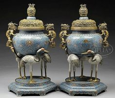 """TWO LARGE CLOISONNE CENSERS.  19th century, China. Surface decorated with formalized lotus scrolling and deer. Supports in the form of three cranes. Repousse gilt dragon handles. Lids of gilt repousse brass with a design of lotus plants. SIZE: 34"""" h x 18"""" w."""