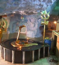 Siva Linga,Tapkeshwar. The Pandavas worshiped Shiva here.     The Shiva Linga here has water dripping down on it through out the year.     The Tapkeshwar Mahadev  cave temple is built upon the banks of a Dehradun seasonal river.     From Dehradoon main city , this temple  is located ~ 5.50 km away towards Garhi Cantonment area .