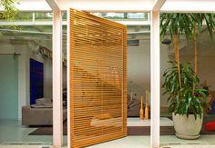 A porta pivotante da entrada, feita com madeira de reflorestamento, ferro e vidro, tem moldura de metal pintado e medidas generosas. Em dias quentes, é possível abrir apenas o vidro, que tem movimento independente