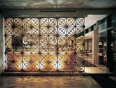 Strong design/pattern used for gold screen divides room and creates interest.