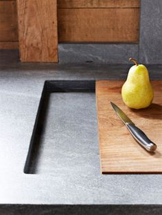 A cutting board is set into the countertop beside each sink, so it's always within reach. It can slide over the sink to make chopping easier or create more counter surface, and then the slot can become a drain board. - Nice!