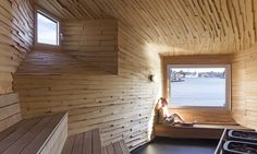 In contrast to the cold-looking facade, the unusually shaped interior is completely covered in large larch shingles for a warm and welcoming appearance.