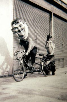 Laurel & Hardy tandem bike ride , giant headed film characters take bike ride presumably for some film promo stunt, surreal and a bit spooky if they suddenly popped up around the corner