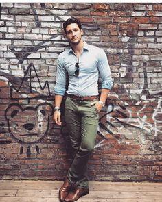 sapato Oxford marrom, calça chino verde escuro, cinto marrom e camisa social azul claro.