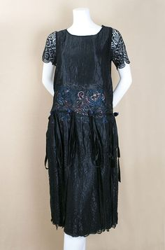 New York silk lace dress, c.1924. Constructed with two separate layers attached at the neckline, shoulders, and drop waist. The slip-style under layer is of black silk chiffon with a skirt lining of black China silk, attached black lace sleeves, and a satin ribbon cummerbund. Its pretty watered silk floral pattern shows through the outer lace—an imaginative design detail. The lace over dress is decorated with velvet ribbon rosettes and streamers that hang from the base of the cummerbund