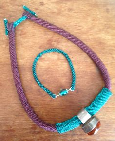 I made.... 45 cm bead crochet rope in matt brown seed beads 11. Square stitch loops. Silver lined turquoise peyote toggles and tube. Amber and silver finger ring as focal. CRAW silver lined turquoise bracelet