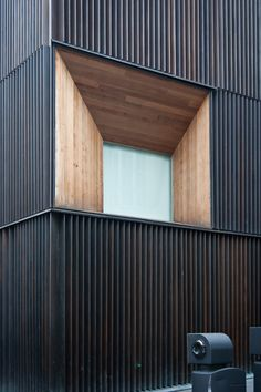 Bronze Facade in contrast to timber and a window.