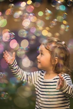 Kid surrounded by soap-bubbles