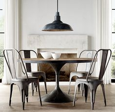 RH's Aero Round Dining Table:Paying homage to the sweeping lines of mid-century furnishings, our table is a study in simplicity. Defined by its balanced proportions and arching, sculptural curves, our interpretation pairs a cast metal pedestal base with a reclaimed wood top repurposed from 100-year-old solid elm doors.