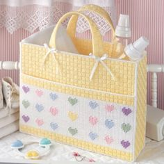 """Heartwarming Baby Tote Plastic Canvas ePattern - This roomy bag for baby's necessities will be a great surprise for an expectant mom! Complete with a big front pocket, it can hold diapers, bottles, rattles, and more. This heart-embellished tote would also make an adorable gift bag for Valentine's Day. The design is stitched using worsted weight yarn and 7 mesh plastic canvas. Number of Designs: 1 tote bag Approximate Design Size: 13-5/8""""w x 15-1/2""""h x 3-7/8""""d"""