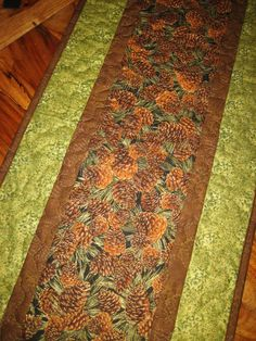 Pine cones outlined in gold set against a black background make up the middle section of this quilted table runner. I used a dark brown fabric for the inner border and outside binding strip, and a green leaf colored fabric for the outer border. A leaf print in fall colors was used for the