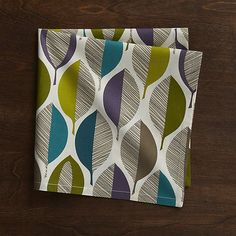 Graphic leaves composed of casual lines and solid cool tones decorate this cloth dinner napkin with rich color and dynamic pattern. Screenprinted on cotton, the dinner napkin pairs with a matching placemat for a lively fall table.
