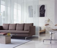In this condo, glass walls delineate the living area and bedroom while allowing light to infiltrate the entire space. A streamlined sofa, sheer drapes, white washed brick walls and glossy flooring combine to create a sleek and modern loft space. Interior Design With Glass, Small House Interior Design, Small Space Design, Glass Design, House Design, Modern Contemporary Living Room, Living Room Modern, Living Room Interior, Living Area