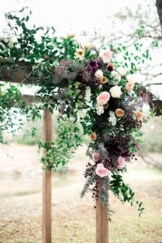 Arch design by Color Theory Collective | The Addison Grove | Asymmetrical design of garden roses, acacia, peonies, ranunculus, amaryllis, smilax | white, ochre, plum, dusty pink, antique tones Photo by Brittany Jean Photo in Austin, TX Venue- The Addison Grove