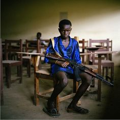 Sekou, a young LURD (Liberians United for Reconciliation and Democracy) rebel sits in an abandoned classroom.