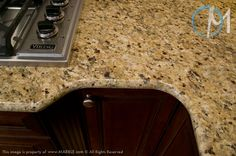 A close up of the Santa Cecilia granite reveals warm yellow highlights and bursts of burgundy flecks.