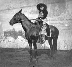 """Della Ferrell, a native of Colorado and member of Buffalo Bill's Wild West Show, poses on horseback in front of a backdrop with a landscape scene painted on it in a dirt arena at Earl's Court in England. Ferrell joined the show in 1887 as one of the """"Western Girls."""" She was a trick rider and roper (1892?)."""