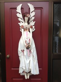 """I enlarged a pattern from one of """"Tilda's"""" designs. The wooden wings are architectural salvage. I made her for one of our Kindred  Heart Stitchers challenges."""