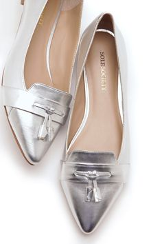 Flat metallic loafers with a front tassel and pointed toe.
