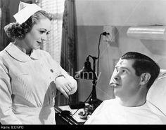 Nurse taking patients temperature © Old Visuals / Alamy