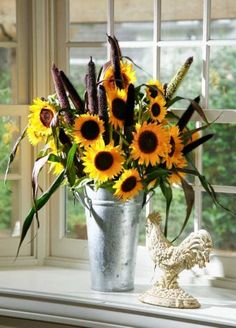 sunflower arrangements can go country or contemporary.  'Purple Majesty' millet and Texas sunflowers in a French flower bucket create an informal arrangement for a kitchen garden window. Photo: John Everett / John Everett