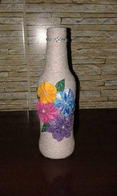Garrafa decorada com barbante com flores de feltro. Linda peça para decorar seu ambiente ou presentear. Peça Única. Ela tem 20cm de altura. R$ 25,90