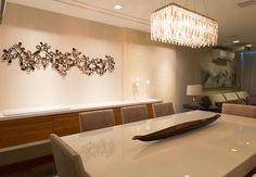 Beleza clean  para sala. Escultura de parede e adorno no centro de mesa, ambas peças são assinadas.  O toque luxuoso está no brilho do ônis envolvendo a parede do aparador e no brilho do lustre de cristais.
