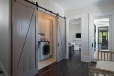 Gray wash bar doors on rails open to a small laundry room fitted with white front loading washing machine placed beneath a black countertop fixed beneath white cabinets.