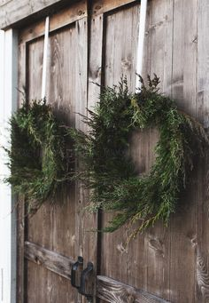 Beautifully made natural pine and cypress wreaths hanging on barn doors for the holiday season providing rustic christmas inspiration and Scandinavian christmas ideas for the holidays wreath creative Natural Christmas, Noel Christmas, Country Christmas, All Things Christmas, Simple Christmas, Winter Christmas, Christmas Wreaths, Christmas Ideas, Christmas Crafts