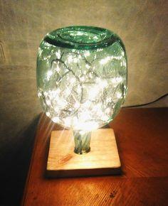 lampara hecho con una damajuana luces led y base de madera