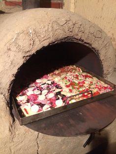 Preparación de pizza casera hecha en horno de barro , a leña.