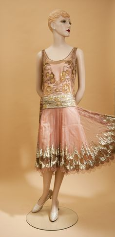 Mid-late 1920s dress of fine silk net decorated with a variety of beads, sequins, and embroidery. A band of pale gold lamé accentuates the drop waist. The sides of the bodice are long rectangular panels covered in elaborate Egyptian influenced ornamentation that extend into the skirt. The skirt is a complete circle that features a scalloped hem with an elaborate flame stitch design of silver sequins and gold beading.