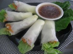 Lumpiang Sariwa / Fresh Spring rolls consist of minced ubod (heart of plam), flake chicken, crushed peanuts and jicamas as an extender in a double wrapping of lettuce leaf and yellowish egg crepe. Served with a sauce of chicken stock, starch mixture and fresh garlic.