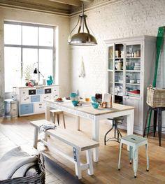 mur de brique exposée blanche, table, banc et tabourets en bois, placard vitré vintage et suspension en métal