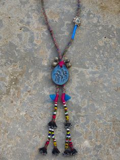 Kinship Stories: Ethnic necklace whose base is made of bohemian printed fabric, using a traditional Turkish technique. The piece of pottery in the center is made by Lebanon-based artist Nicole Bruno. Attached to it are vintage mixed silver beads from Yemen (30k). The tassels are Uzbek, originally part of a piece of hair adornment. The triangular blue glass beads are Afghani amulets, worn for protection. The star-shaped button is Nepali and is made of Yak horns (Himalayan bull).