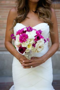 Pink and purple roses add a pop of color against the bride's strapless white gown. Wedding Floral and Event Design: Posh Peony Floral and Event Design.