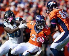 Denver Broncos running back Montee Ball (28) fights off defender Jacksonville Jaguars defensive end Andre Branch (90) in the first quarter o...