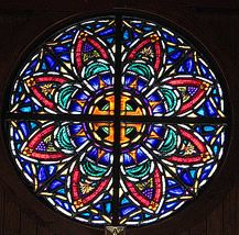 This stained glass window is at All Saints' Episcopal Church in Tybee Island, Georgia. The hub is the Canterbury Cross.   The cross gets its name from its birthplace and is commonly seen in Canterbury, United Kingdom.