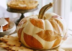 Leafy centerpiece: Display your favorite fall foliage colors with simple decoupage (gluing flat objects or pictures to a surface). Real leaves applied to a white pumpkin set a sophisticated scene.