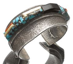 A Hopi bracelet Unsigned, sold as the work of Charles Loloma, tufa cast, the two-tiered asymmetrical cuff supporting a topographical mosaic band of turquoise, ironwood, walrus ivory, coral and abalone tiles, an integral lightning bolt motif at one end. width 2 3/4in