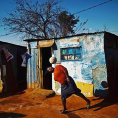 A South African woman, bounces the ball on her head while playing with a football with other women, not seen, next to their homes in a Soweto township. This is the latest photo from the December magazine, available online tomorrow. African Tribes, African Women, Fifa World Cup, Things That Bounce, South Africa, Landscapes, Art Gallery, Childhood, Homes
